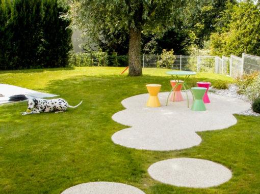 Chemin moderne et familial particulier, dalles circulaires et mobilier coloré avec installation de pelouse
