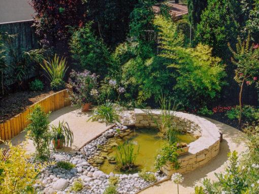 Aménagement d'un mur en galet entourant un bassin végétal