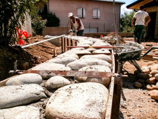 Création par les maçons Valente de murets en galets dans un jardin de particulier